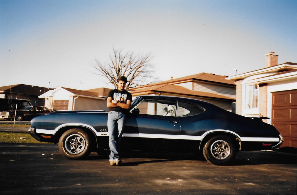 Figure 2  Photograph of my dad leaning on the restored Oldsmobile 442 W30 outside of their new house on Elliot street.