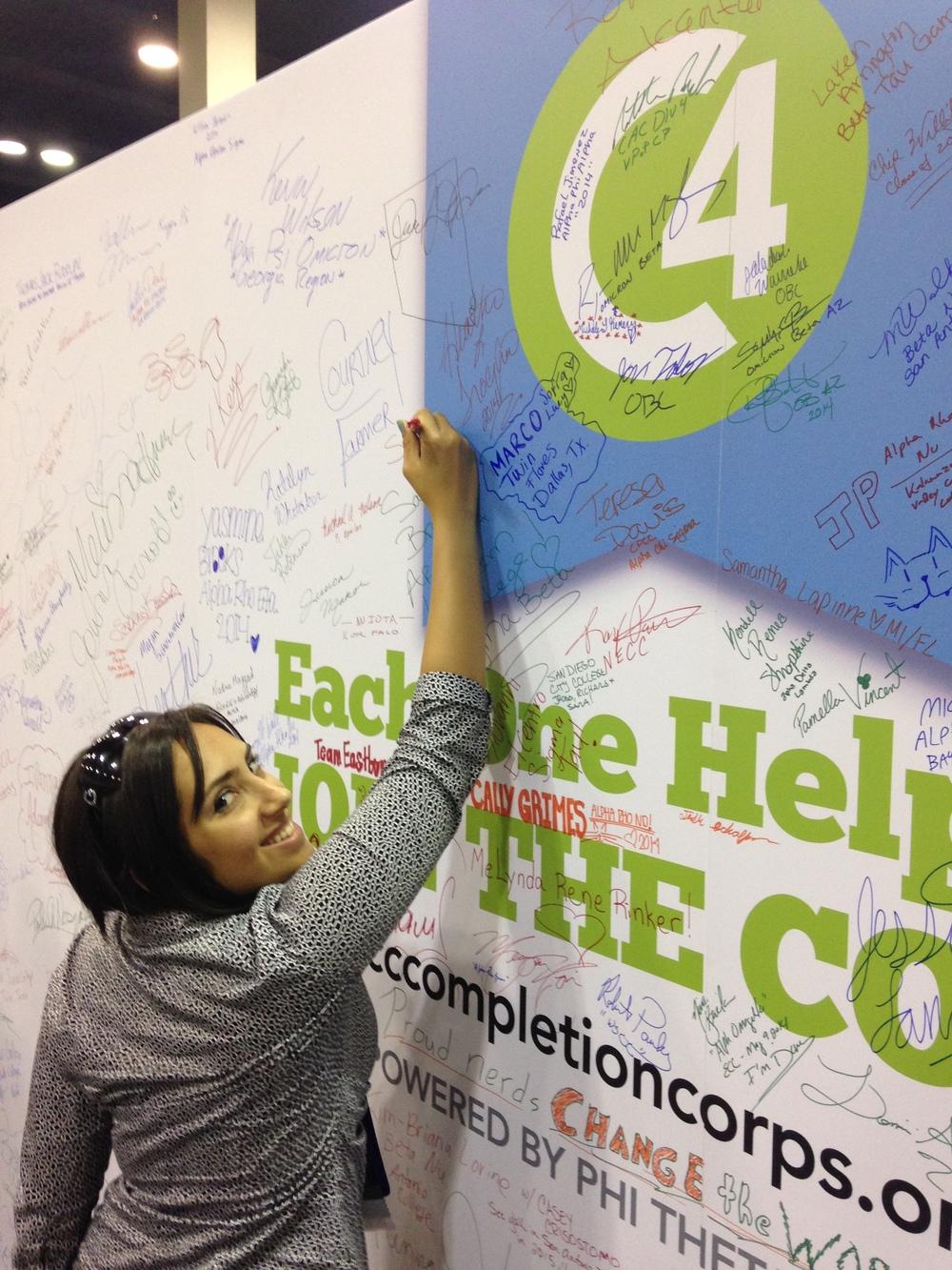Sara signing the C4 poster