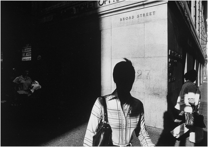 Solitary pedestrians and urban spaces transformed by sunlight and shadow. Image © Ray Metzker