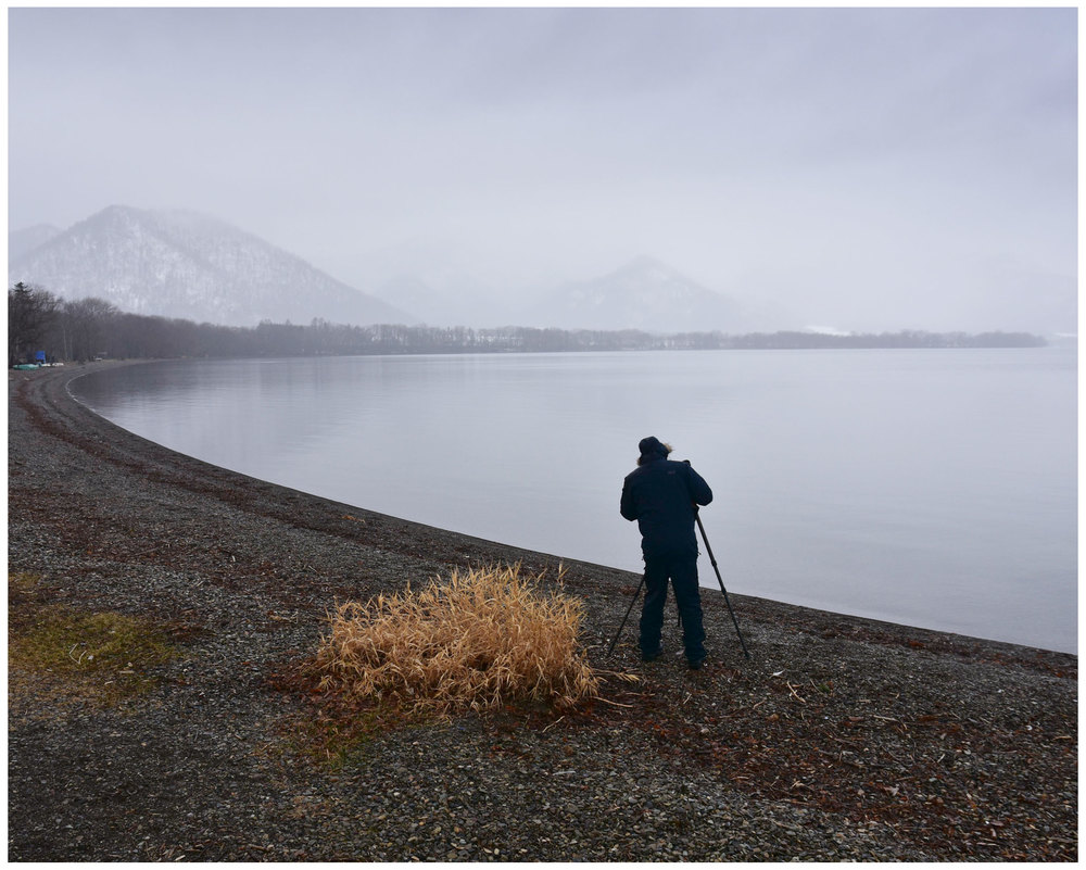 Me photographing at the edge of beautiful lake Kussharo, Hokkaido Japan, December 2015.