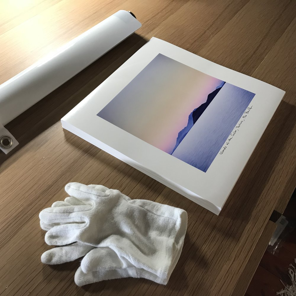 When handling prints, it's a good idea to use cotton gloves, so that any natural oils in your skin don't blemish the paper. Above is a stack of prints that had a natural curl in the paper. The curl has been removed by the de-roller.