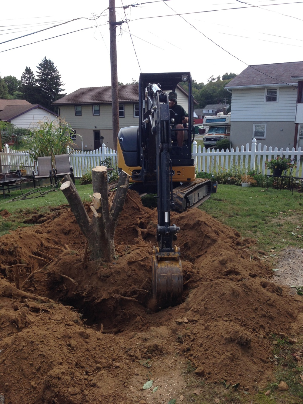 BLS removing a stump from a yard with an excavator to make sure the entire stump is out in order to put a patio in for a customer.