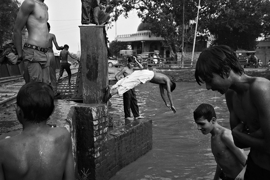 As a way to beat the oppressive Pakistani heat the muddy, sewage filled canals in Lahore become a summertime swimming hole, as lower-class boys of all ages jump from a bridge into the water. © Melissa Lyttle