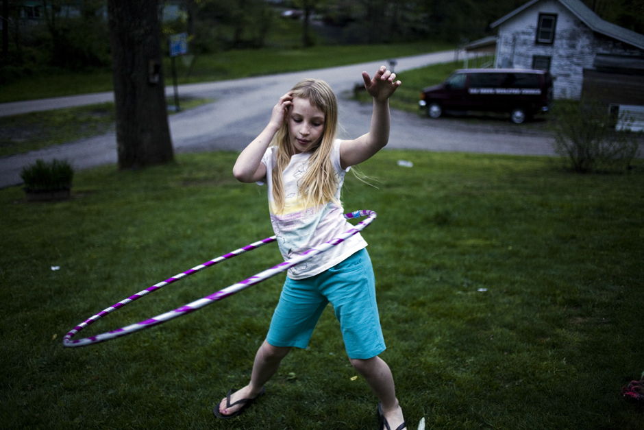 """Sonya Casto plays with a hula hoop in her grandmother's front lawn. Sonya, who is 11, suffers from Post Traumatic Stress Disorder from living with her mother and her boyfriend who abused her for years. """"My mother doesn't know how to be a mom. She's no mother to me,"""" Sonya says. Sonya is currently being taken care of by her grandmother. © Maddie McGarvey"""