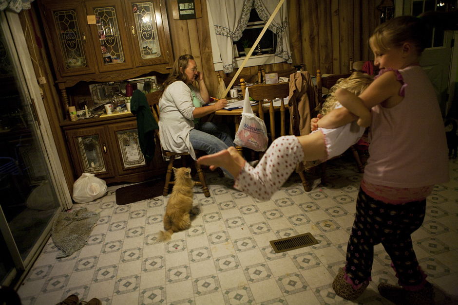 Sonya plays with her little sister Paige in the kitchen of her grandmother's home while Lorrie tries to figure out medication bills for her grandchildren. Lorrie has had to sacrifice much of her life savings and golden years to raise her grandchildren.© Maddie McGarvey