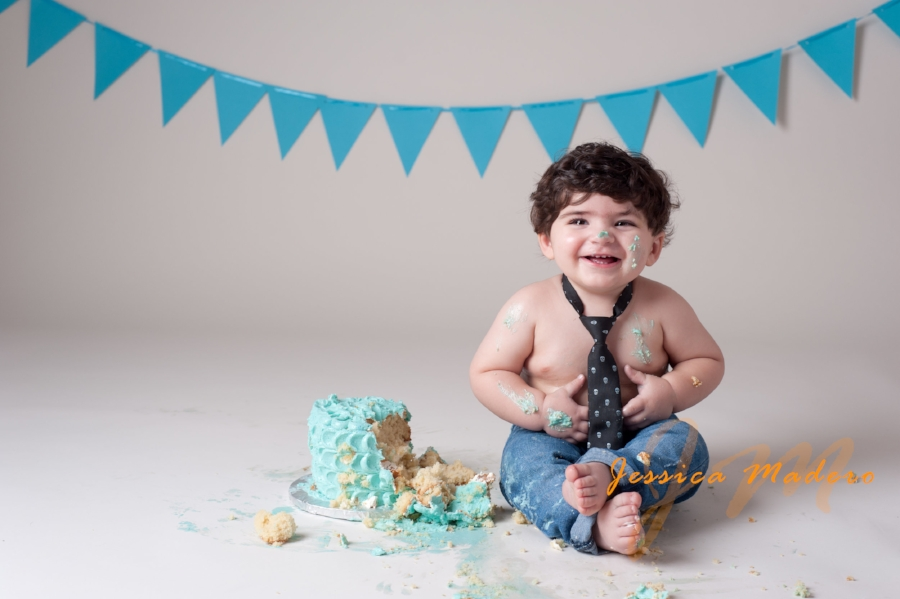 Baby boy one years old with a black neck tie and jeans laughing and smashing cake for his Cake Smash Session in Staten Island, NY