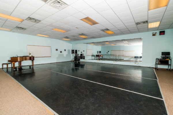 Studio 5 26' x 31' dance space with professional grade sprung wood floor, Marley dance floor covering, full-length glassless safety mirrors, a grand piano, 25 folding chairs, and an full sound system.