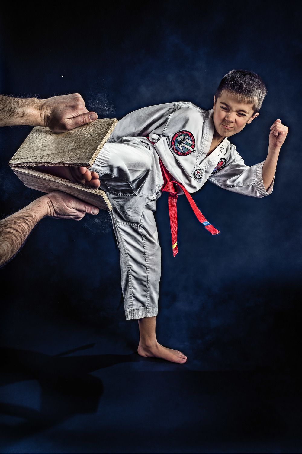 Taekwondo boy kicking a board.