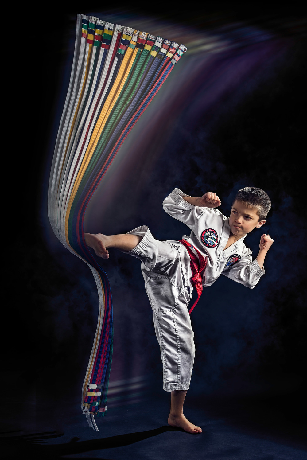 Taekwondo boy kicking at his belts.