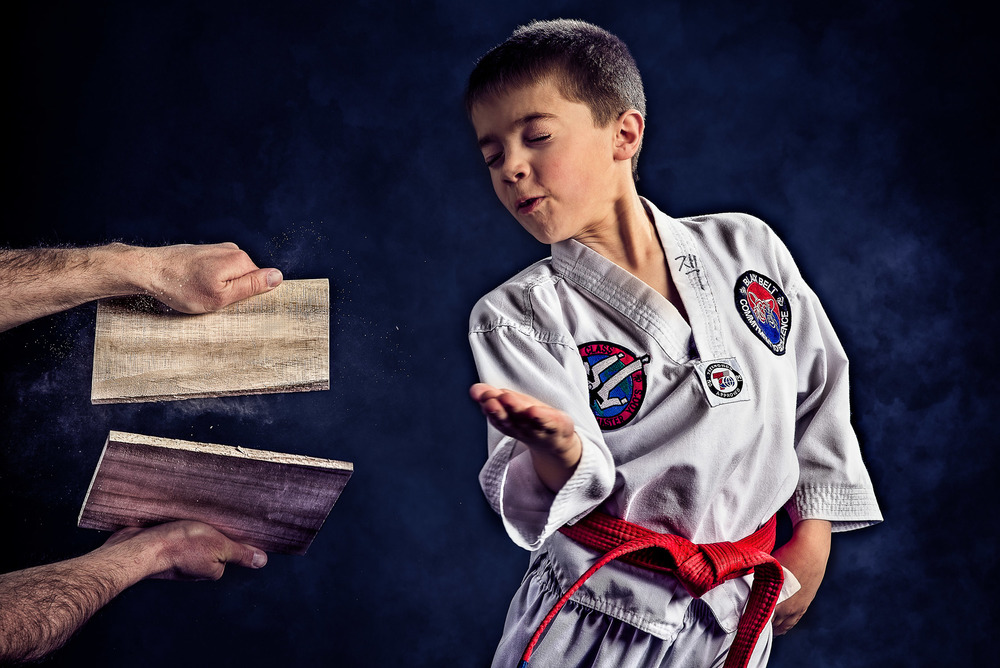 Taekwondo boy breaking a board with his hand
