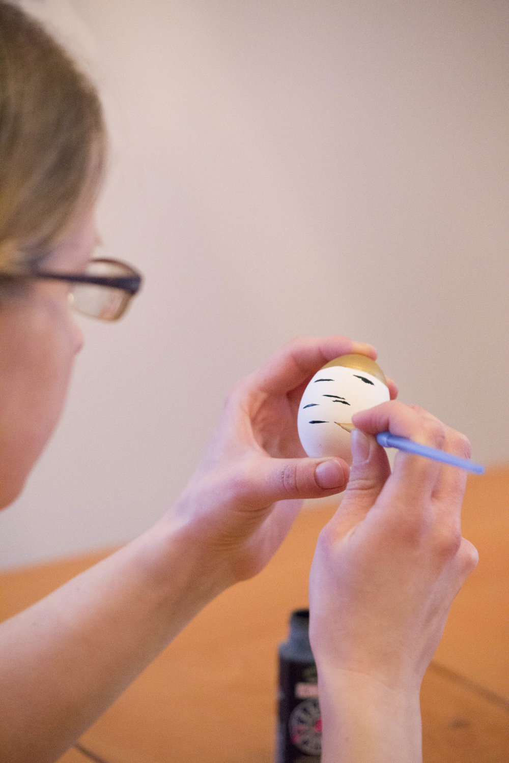 Hand-painting a birch bark design to the egg.
