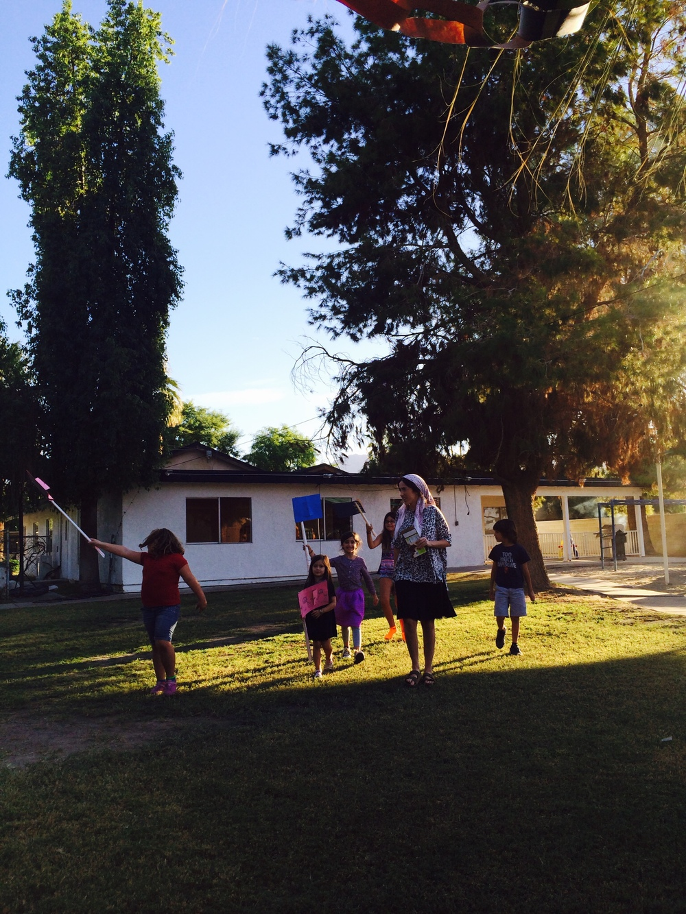 A few of Morah Dina's students march to the Sukkah with their Simchat Torah flags!