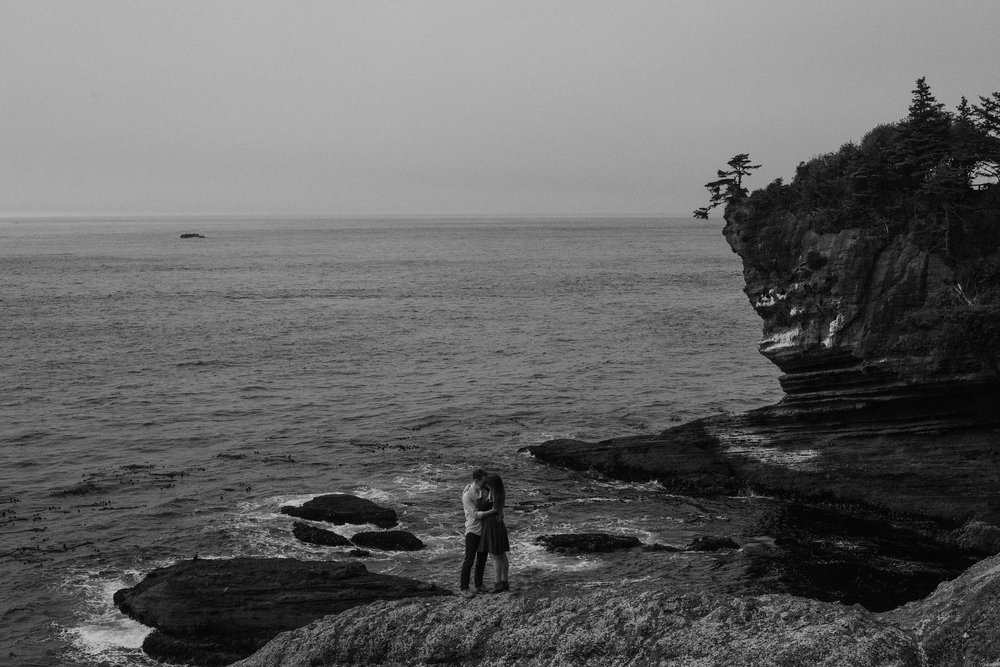 Couple holding each other on rocky Washington coast.