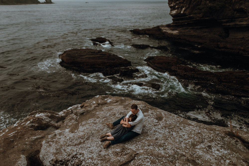 Couple sitting on ocean cliff rock at sunset.