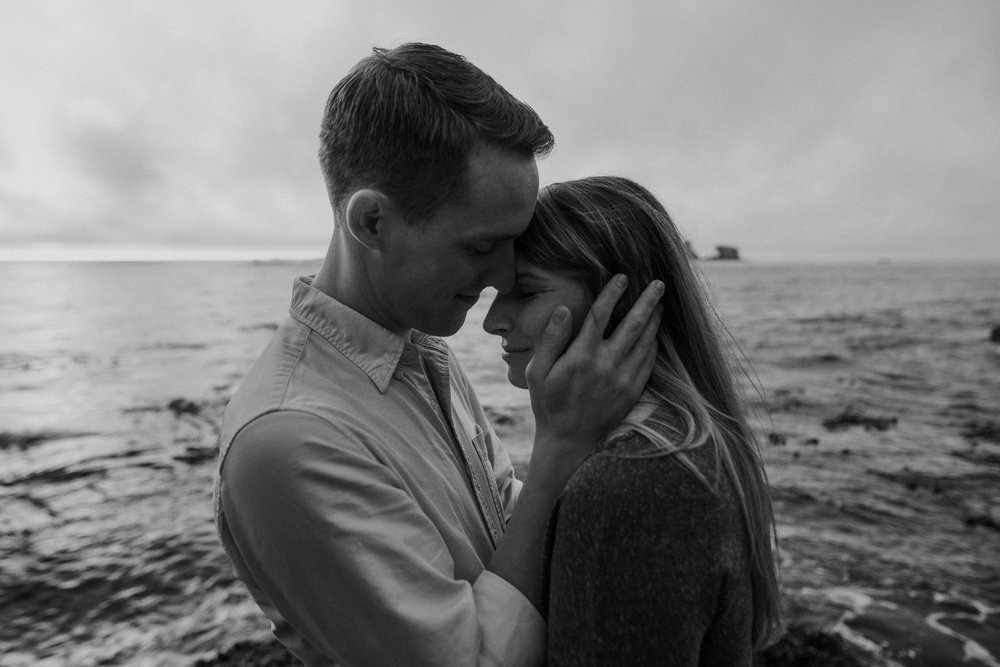 Couple holding face at the ocean.