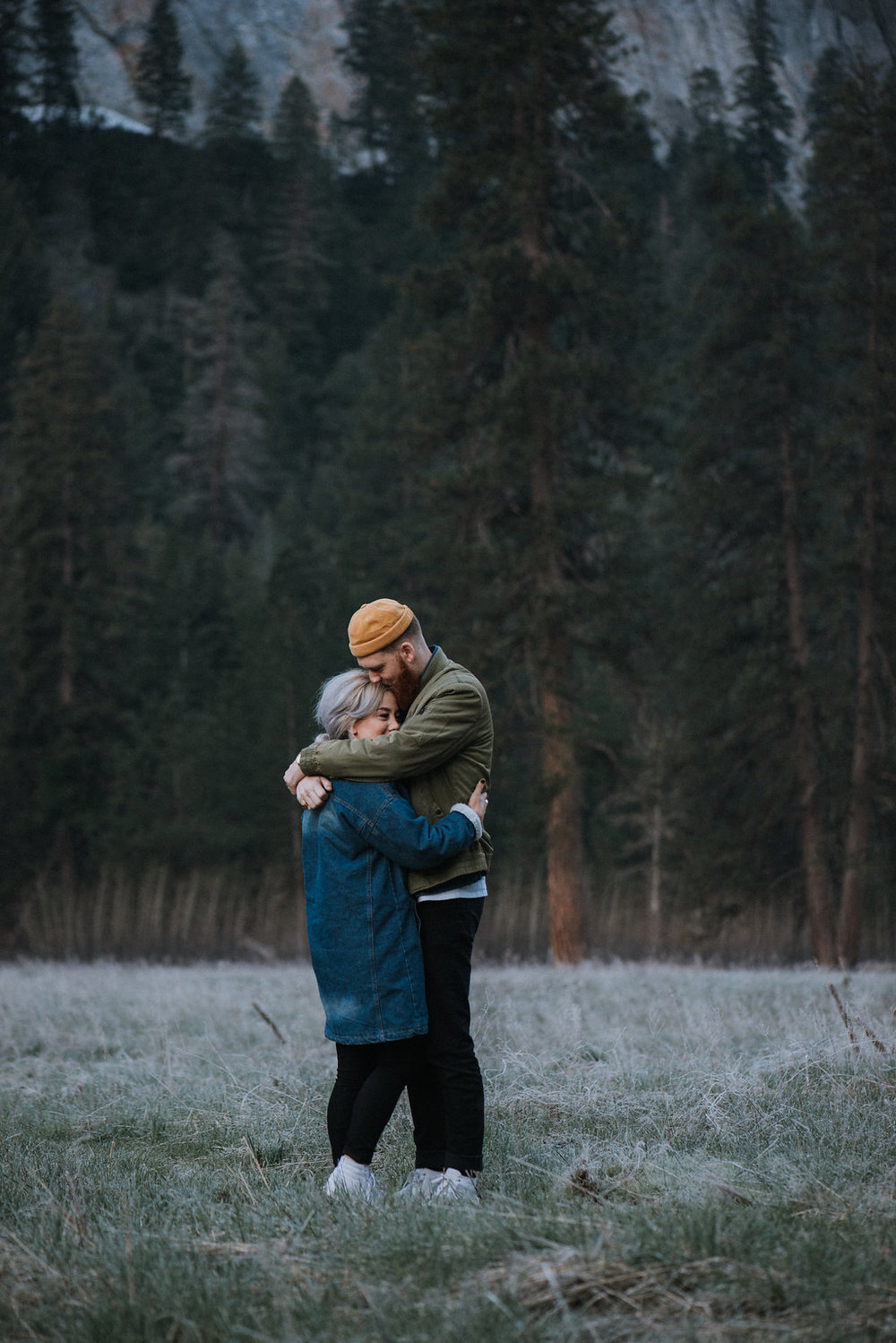 Couple holding each other smiling at sunrise in Yosemite Valley.