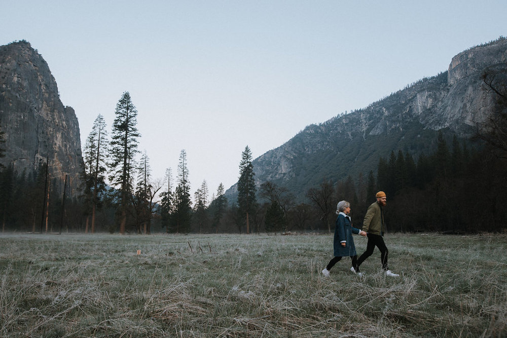 Couple holds hands and walks in Yosemite Valley.
