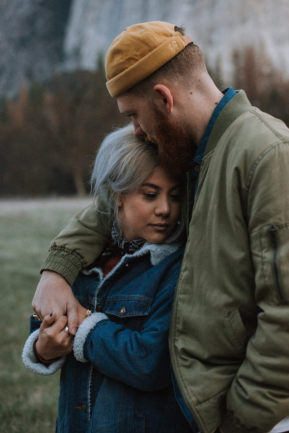 Man holds woman in jacket in Yosemite National Park.