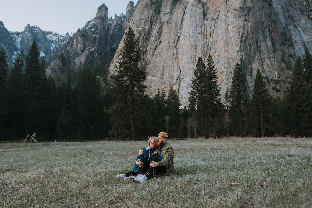 Couple holds each other in Yosemite Valley at sunrise.