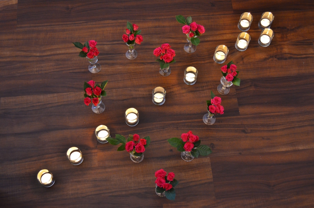 "A grand gesture of love, done on a budget. I used simple white votive candles inside glass holders and multiple flower clusters inside my cordial glasses to create a romantic heart and arrow. You can re-create this at home on your dining table, on the floor of your bedroom entrance (naughty, naughty!), or even as part of a proposal. I can see the ""little blue box"" right in the middle of the heart!"