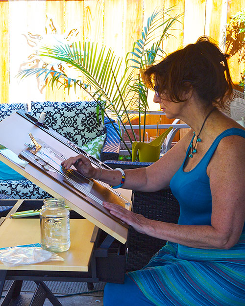 Linda at work with her watercolors in her inspiring California backyard.