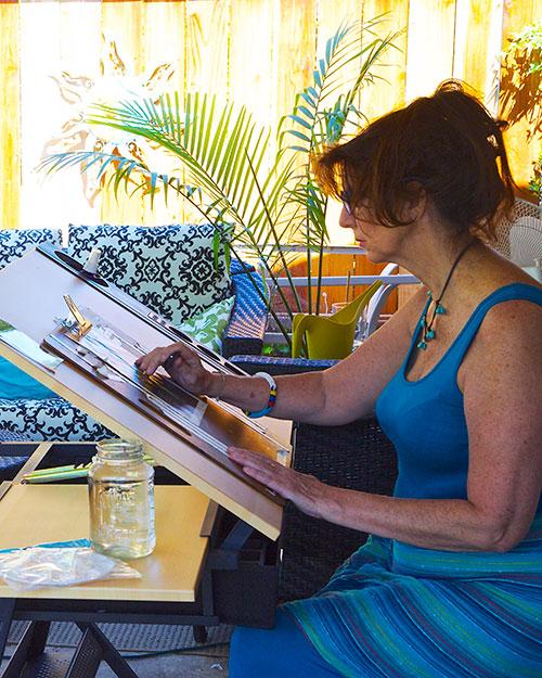 Linda at work with her watercolors in her inspiring California backyard.