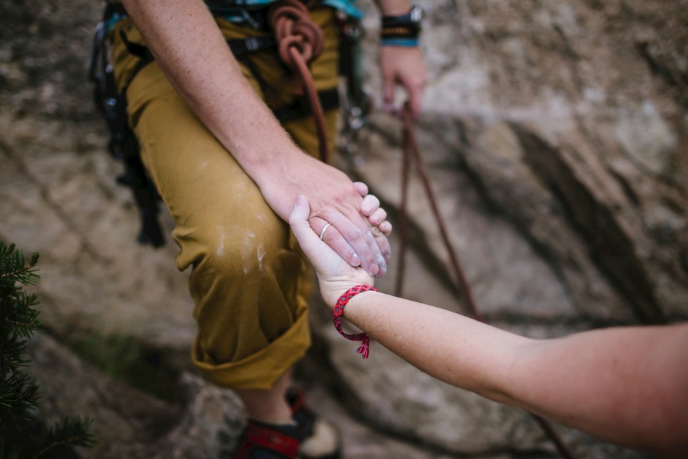 Love this shot of a couple holding hands while rock climbing with chalk // Adventurous Engagement Photographer //  Maddie Mae Photography