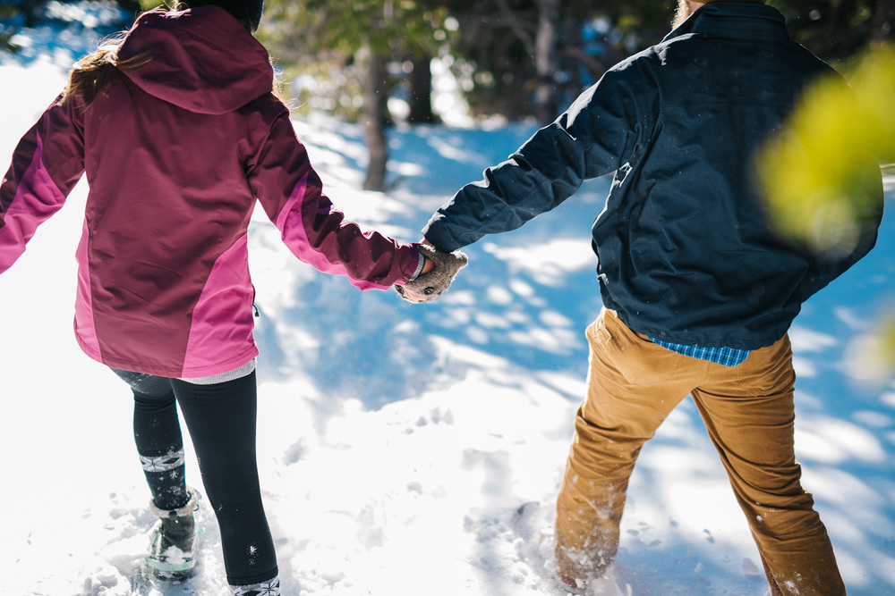 Couple holding hands while snowshoeing during this snowshoe engagement session. Photos by Maddie Mae Photography