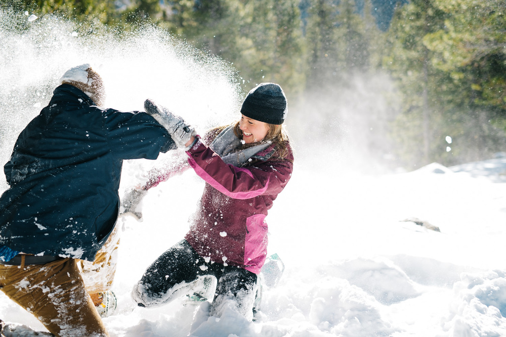 Playing in the snow during a winter engagement session photo shoot by Maddie Mae Photography