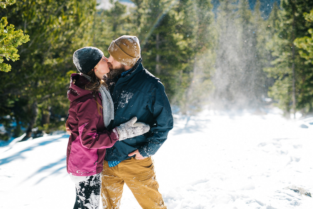 Kissing while covered in snow. Snow fight, playing in snow, engagement photoshoot by Maddie Mae Photography.