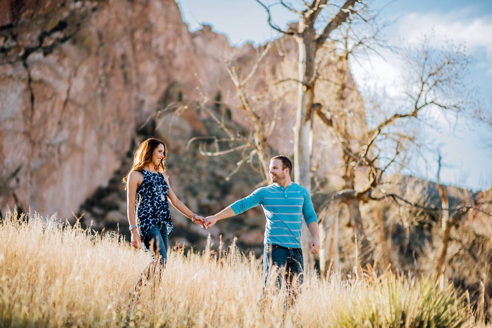Couple walking through a backlit grass meadow on an engagement shoot at Garden of the Gods in Colorado Springs, CO. Adventurous engagement photos taken by Maddie Mae Photography.