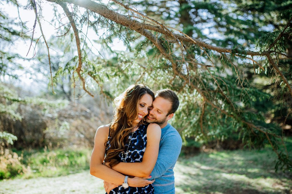 Colorado Springs engagement shoot. A couple cuddles underneath pine trees. Photos by Maddie Mae Photography.