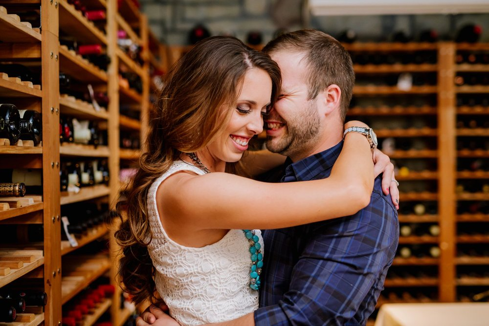 A couple embraces in a private wine cellar on their winery engagement shoot by Maddie Mae Photography - Colorado Adventure wedding photographer.