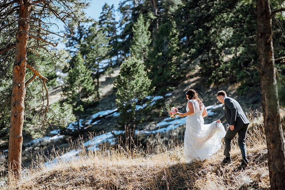 It's so cute how the groom is holding the bride's dress. Estes Park is so beautiful! What a nice mountain wedding venue. Photo by Maddie Mae Photography