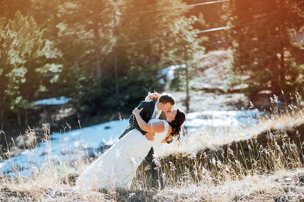 This dip kiss pose is so cute with the sunlight like that. Mary's Lake Lodge is an incredible wedding venue- especially with snow still on the mountains up in Estes Park! Photo by Maddie Mae Photography