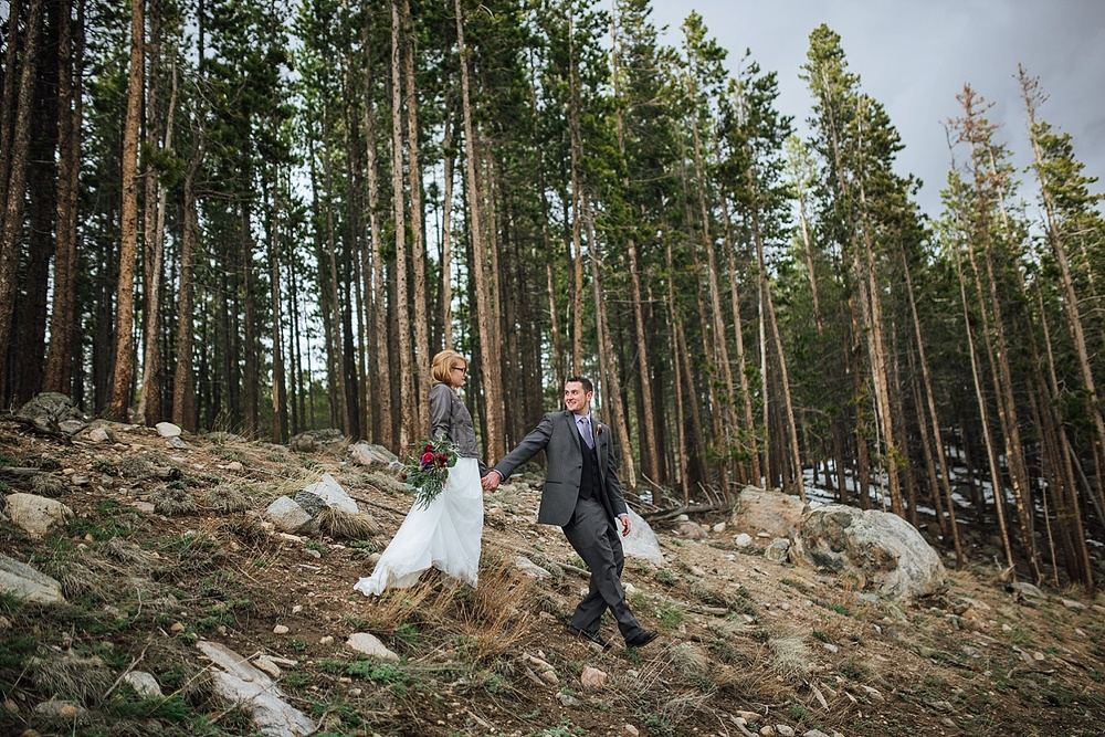 I love how the groom is leading her down the hill with all those trees in the background. I love hiking around Rocky Mountain National Park... Maybe I'll have my wedding there.. Photo by Maddie Mae Photography