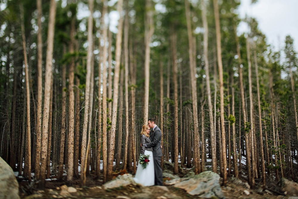 I love how the trees look behind this couple. She is so smart to wear a jacket on top of her dress, especially with all that snow on the ground! Photo by Maddie Mae Photography