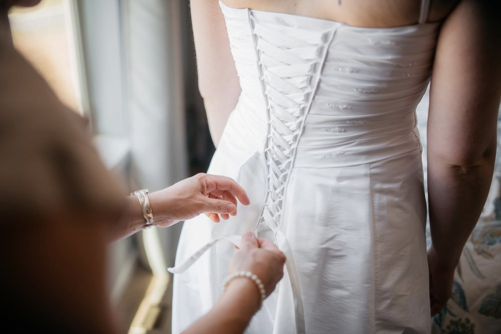 The lace up corset on the back of this wedding dress is a beautiful feature. I love these getting ready photos! Photo by Maddie Mae Photography