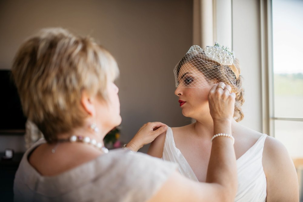 Beautiful picture of a bride getting ready and having her birdcage veil adjusted. I love this kind of veil- might have to get one for my wedding! Photo by Maddie Mae Photography
