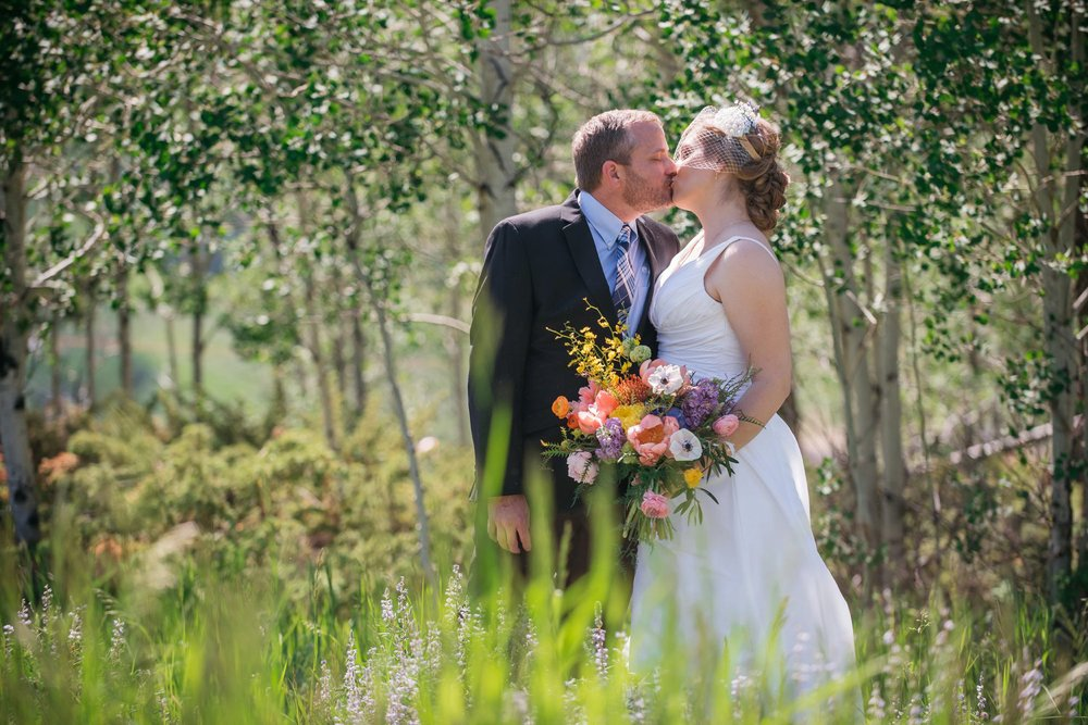 This mountain meadow is stunning for wedding photos! I love how her wildflower bouquet blends with the tall grass and trees!  Photo by Maddie Mae Photography