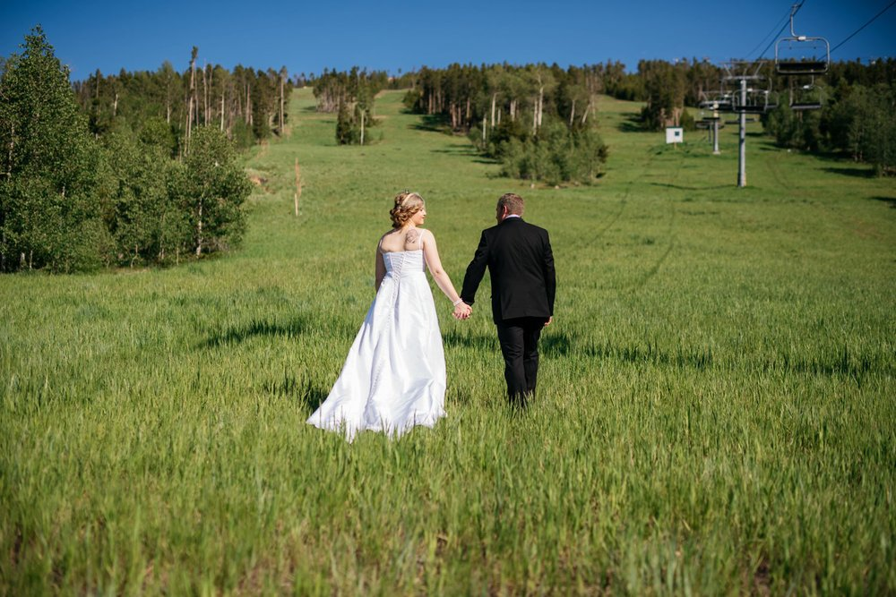 Bride and groom holding hands and walking up the mountain next to a ski lift. This is a must do for a Colorado mountain wedding in the summer! Photo by Maddie Mae Photography