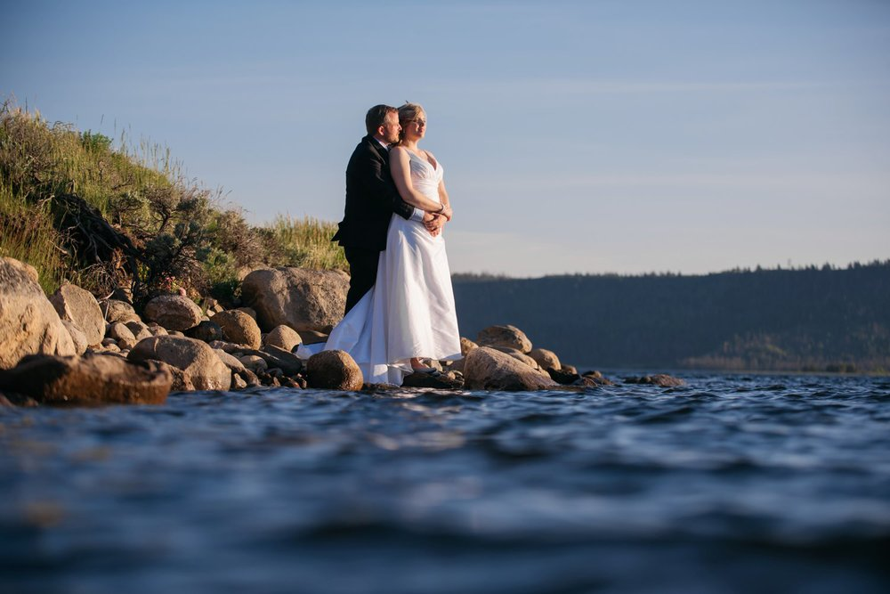 Bride and groom wedding photos taken on the rocky shore of Grand Lake in Colorado. Photo by Maddie Mae Photography