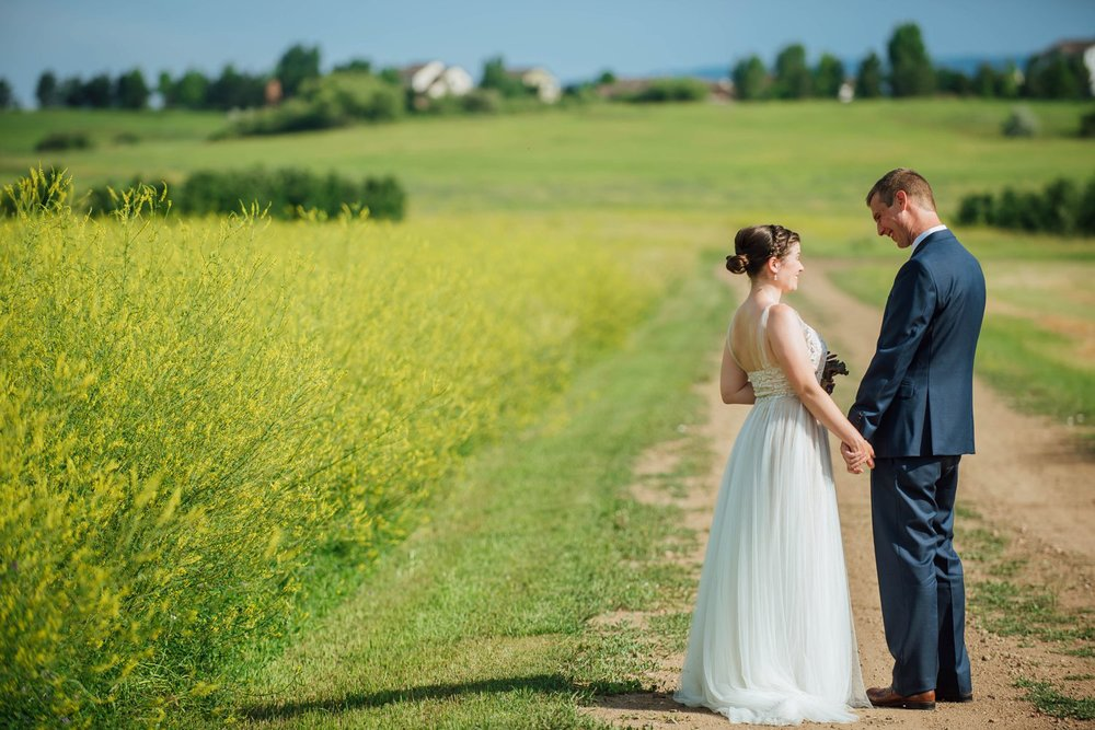 I love this dirt road that runs parallel to the field with the tall grass for wedding photos! Photo by Maddie Mae Photography