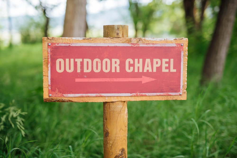 I love this outdoor chapel sign that can direct guests to the wedding ceremony site. Photo by Maddie Mae Photography