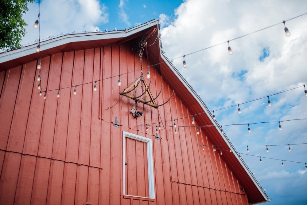 I love the string bulb lights hanging from the red barn at Chatfield Farm for a wedding reception. Photo by Maddie Mae Photography