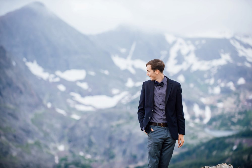 I love how misty and snowy the mountains look behind this groom. Photo by Maddie Mae Photography
