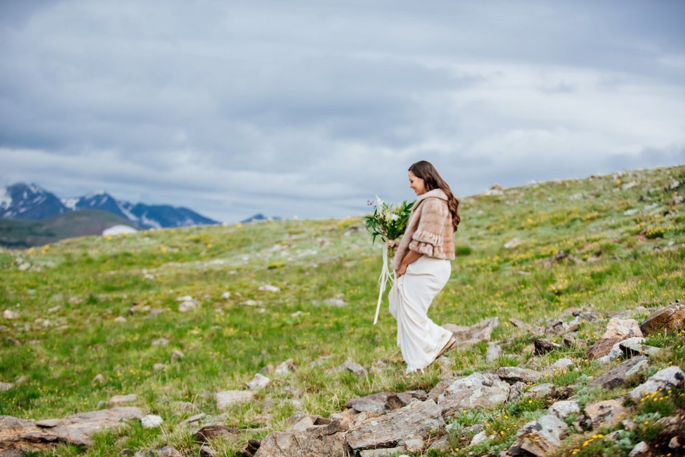 The bride walks down the hill in a Colorado mountain wedding. Photo by Maddie Mae Photography