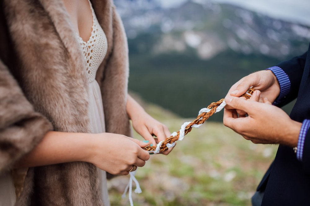 Her knitted dress and fur coat are so perfect for this mountain wedding. I also love this braid ceremony. Photo by Maddie Mae Photography