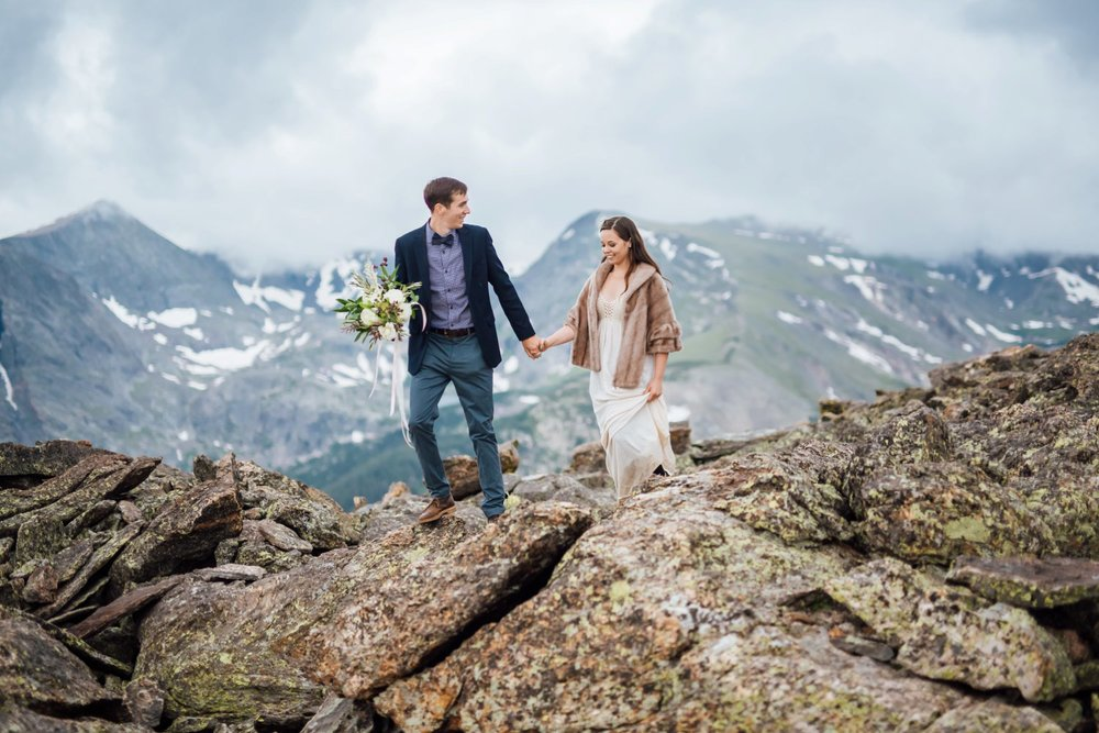 I love the bride and groom hiking over these giant rocks in the mountains for their wedding photos. Photo by Maddie Mae Photography