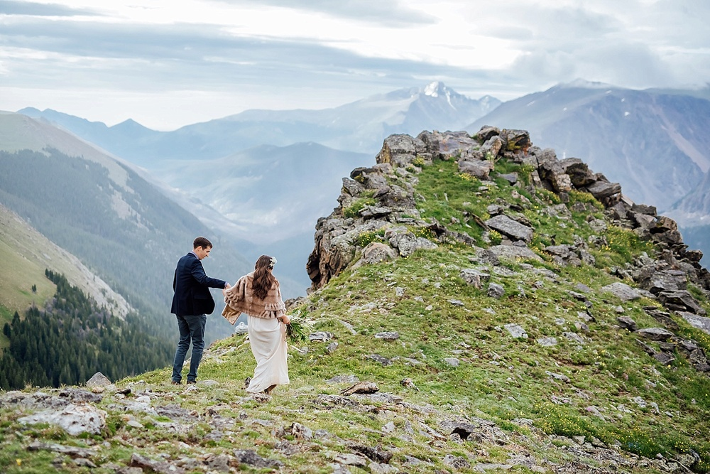 The bride and groom explore the mountain tundra after their epic elopement in Rocky Mountain National park. Colorado elopement photographer, Maddie Mae Photography.